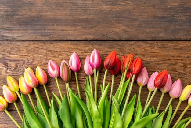 Tulpen in verschiedenen farben auf holztisch, bogenförmig, kopierraum