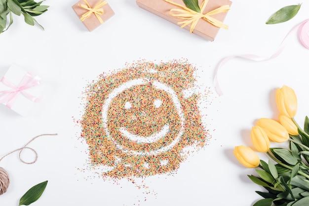 Tulpen, kästen mit geschenken und bändern um die süßigkeit in form eines smiley