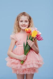 Tulpen. kleines mädchen mit frühlingsblumen in der hand, im rosa kleid, lokalisiert auf blauer wand