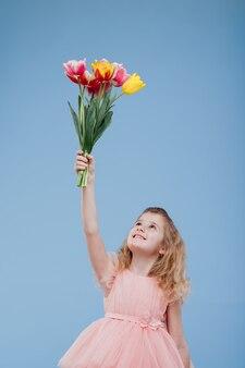 Tulpen. lächelndes kleines mädchen nimmt einen blumenstrauß der frühlingsblumen im rosa kleid auf, lokalisiert auf blauer wand