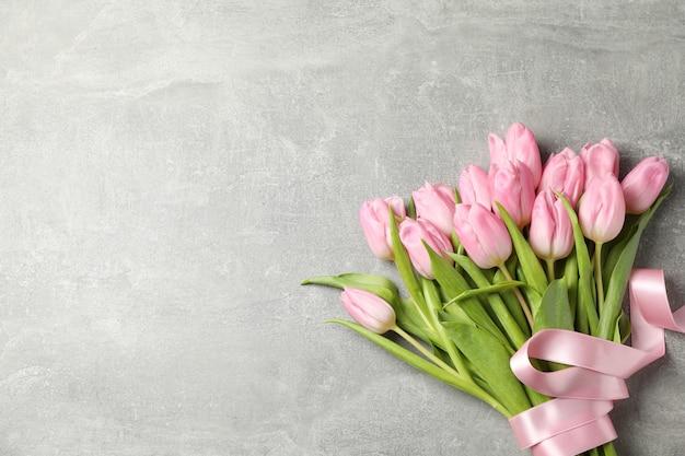 Tulpen mit band auf grauem hintergrund, draufsicht