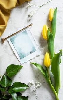 Tulpen mit grußkarte auf dem tisch