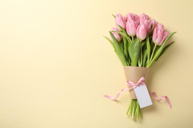Tulpen mit leerem etikett auf beigem hintergrund, platz für text