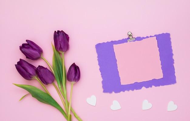 Tulpen mit leerem papier und kleinen herzen