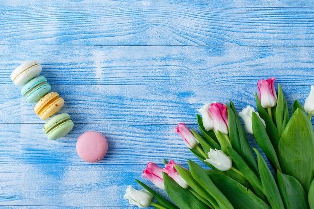 Tulpen mit makronen auf blauem hölzernem hintergrund. rustikale tulpen.
