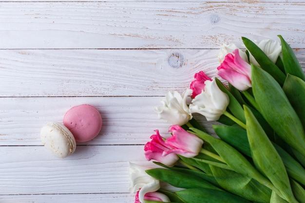 Tulpen mit makronen auf weißem hölzernem hintergrund. rustikale tulpen.