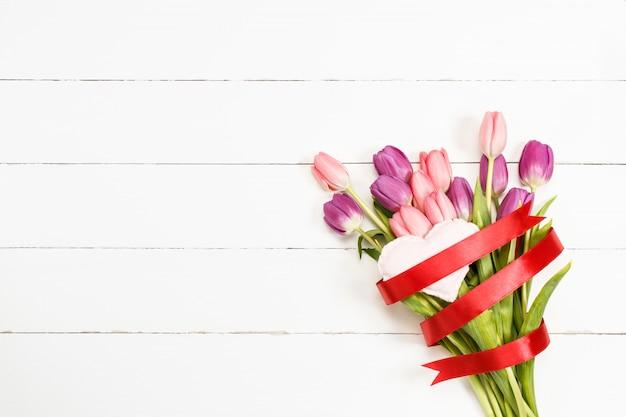 Tulpen mit rotem band- und gewebeherzen auf weißem hölzernem hintergrund.
