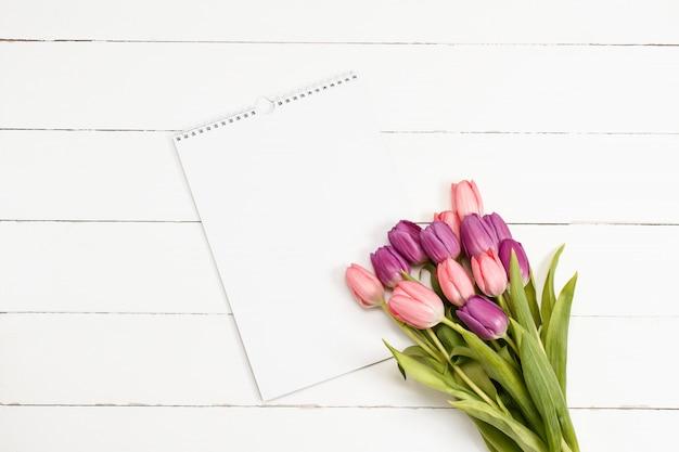 Tulpen mit weißbuch auf hölzerner beschaffenheit. flat lay für valentinstag singen vorlage