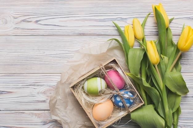 Tulpen und eier auf hölzernem hintergrund