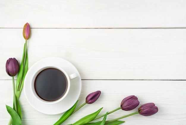 Tulpen und eine tasse kaffee auf hellem hintergrund. draufsicht mit platz zum kopieren.