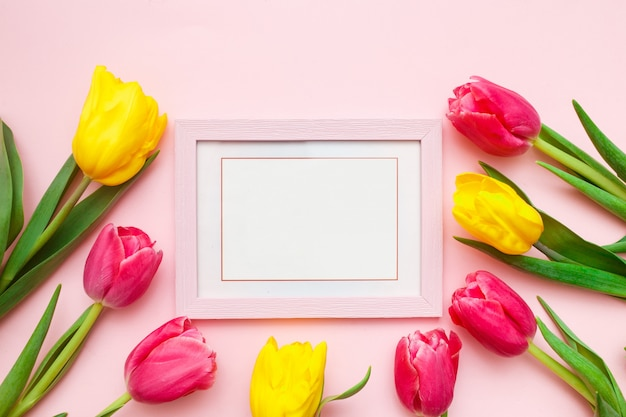 Tulpen und fotorahmen auf rosa