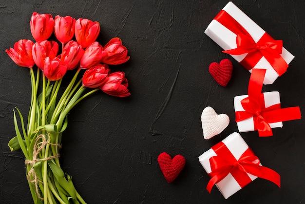 Tulpen und geschenke auf schwarzem hintergrund