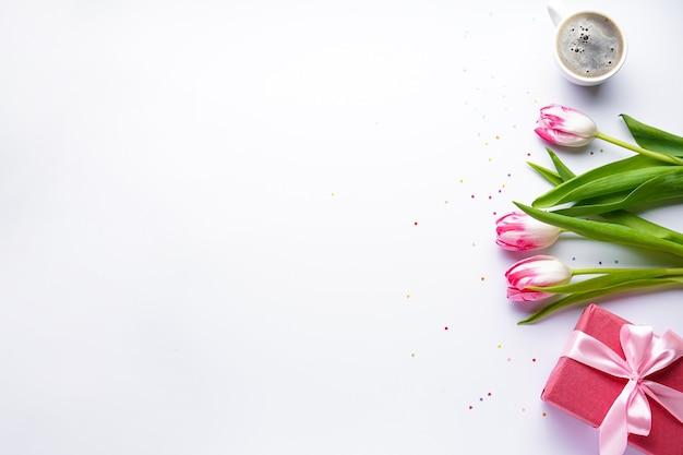 Tulpen und kleine herzen mit kaffee, eine geschenkbox auf einem weißen hintergrund, mit kopienraum. flach liegen.