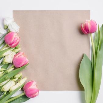 Tulpen und rosen in der nähe von papier