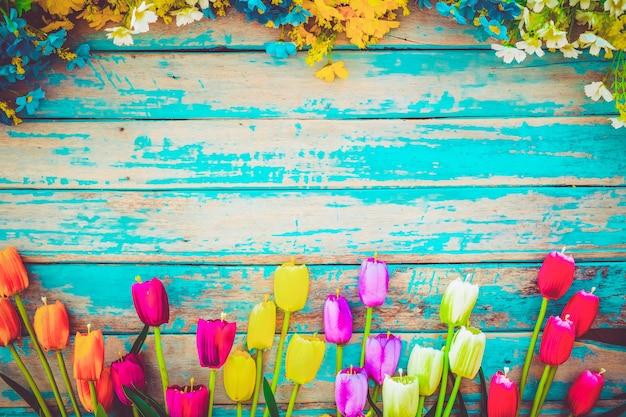 Tulpenblüte blüht auf hölzernem hintergrund der weinlese, grenzrahmendesign. weinlesefarbton - konzeptblume des frühlings- oder sommerhintergrundes