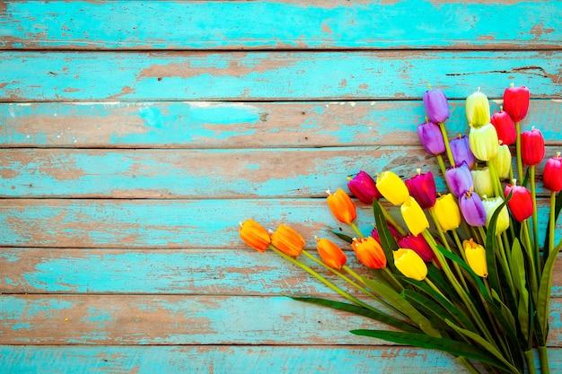 Tulpenblütenblumen auf hölzernem hintergrund der weinlese