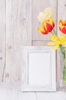 Tulpenblume in glasvase mit bilderrahmendekor auf holztischhintergrundwand zu hause, nahaufnahme, designkonzept zum muttertag.