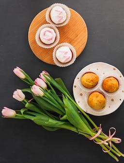 Tulpenblumen mit kleinen kuchen auf tabelle