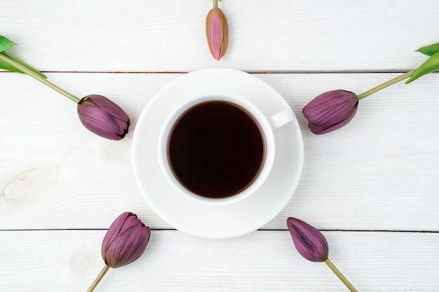 Tulpenblumen um eine kaffeetasse auf einem hellen hintergrund. draufsicht mit platz zum kopieren.