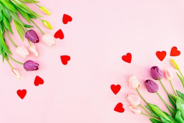 Tulpenblumen und rote herzen auf rosa