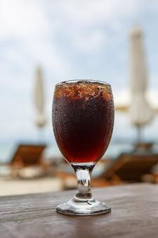 Tulpenglas mit cola auf dem tisch. sonnenschirme