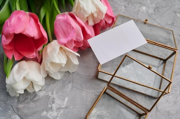 Tulpenrahmen und grußkarte auf grunge grauem tisch. blühende frühlingsblumen, frische blumendekoration, grüne frische, romantisches geschenk
