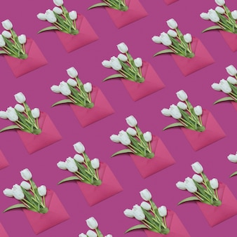 Tulpensträuße im handgefertigten umschlagmuster auf magentafarbenem hintergrund. postkarte für glückwünsche. flach liegen.