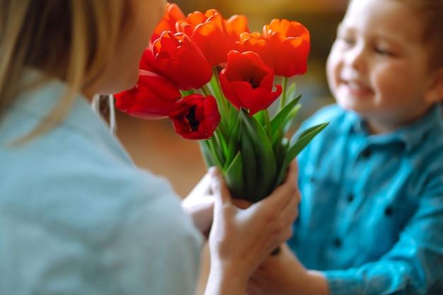 Tulpenstrauß für mama. der kleine sohn gratuliert der mutter und schenkt einen blumenstrauß tulpen. schönen muttertag.