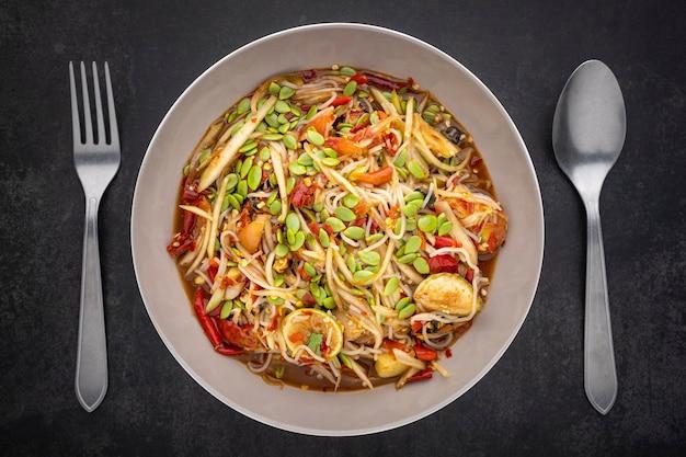 Tum pa, som tum, thailändisches essen, würziger papayasalat mit thailändischen reisnudeln, goldene apfelschnecke (pomacea canaliculatalamarck), leucaena leucocephala samen (lamksamen), limette, tomate, eingelegter fisch und chili