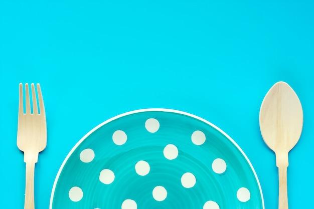 Tupfenplatte mit hölzernem löffel und gabel auf blauem hintergrund