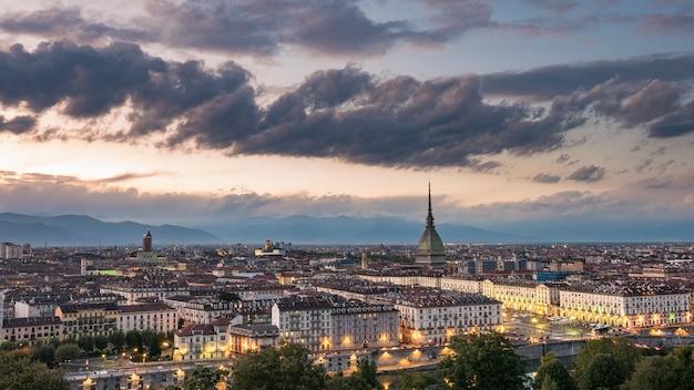 Turin-stadtbild, italien. panoramablick der skyline von turin, italien, an der dämmerung mit glühenden stadtlichtern. die mole antonelliana beleuchtet, szenische wirkung.