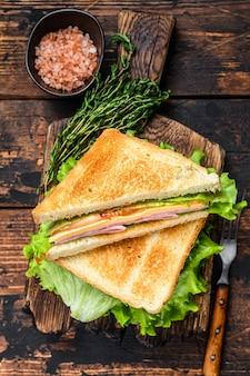 Turkey ham club sandwiches mit käse, tomaten und salat auf einem hölzernen schneidebrett. dunkler holztisch. draufsicht.