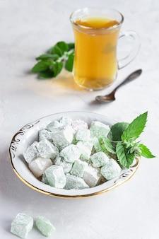Turkish delight lokum auf einem teller mit einem glas tee