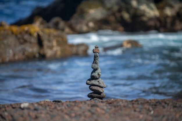 Turm aus steinen auf seestrandhintergrund. entspannen am tropischen strand mit steinstapel.