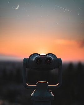Turmbetrachter, der in richtung roten sonnenuntergang mit sternen und mond schaut