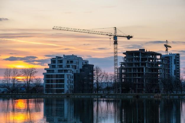 Turmdrehkrane und hohe wohngebäude im bau am seeufer. immobilien-entwicklung.
