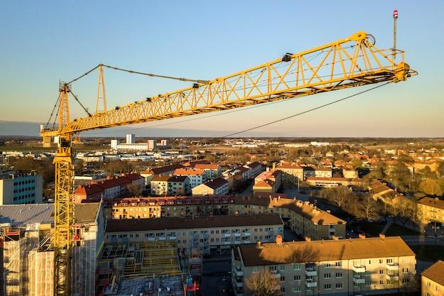 Turmkran auf hellem kopienraumhintergrund des blauen himmels, stadtlandschaft, die zum horizont ausdehnt. luftaufnahmen mit drohnen.