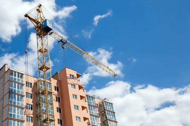Turmkran, der neues modernes wohnhaus auf einem hintergrund des blauen bewölkten himmels am sonnigen tag errichtet.