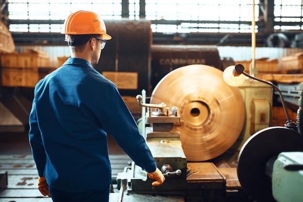 Turner in uniform und helm arbeitet an drehbank, fabrik. industrielle fertigung, schlossereitechnik, kraftmaschinenbau