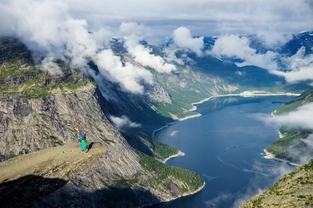 Turner steht auf seinen händen am rand mit fjord im hintergrund in der nähe von trolltunga. norwegen.