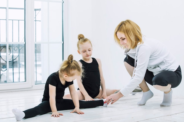 Turnerinnen und tänzerinnen von kleinen mädchen, die sich mit einer trainerin in einem hellen raum glücklich und niedlich dehnen