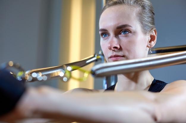 Turnhallenfrau pilates, das sport im reformerbettlehrermädchen ausdehnt. tiefenschärfe auf die hände