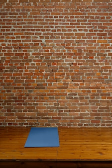 Turnhallenmatte auf hölzernem podium mit backsteinmauer auf hintergrund