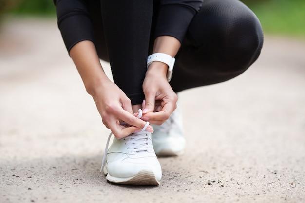 Turnschuh-problem, weiblicher läufer, der ihre schuhe sich vorbereiten für einen stoß bindet