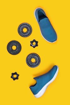 Turnschuhe und kettlebells auf gelb.