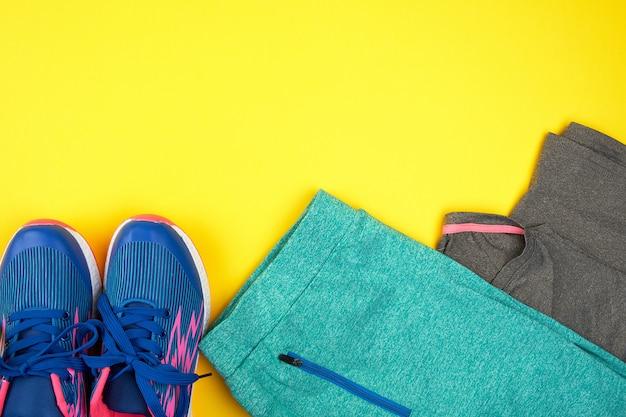 Turnschuhe und kleidung der blauen frauen für sport auf einem gelben hintergrund
