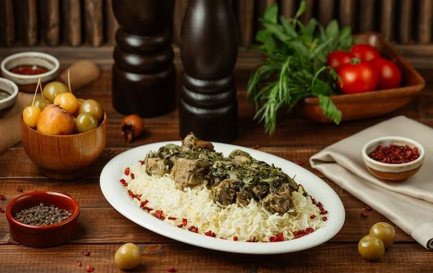 Turshu govurma plov mit fleischstücken und reis garnieren