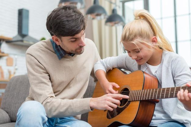 Tutor hilft seinem jungen schüler beim gitarrenspielen