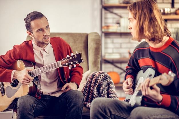Tutor im sessel. professioneller junger gitarrenlehrer, der im sessel sitzt und mit seinem schüler spricht