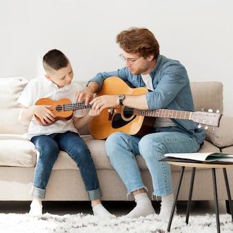 Tutor und junge lernen akustikgitarre und ukulele